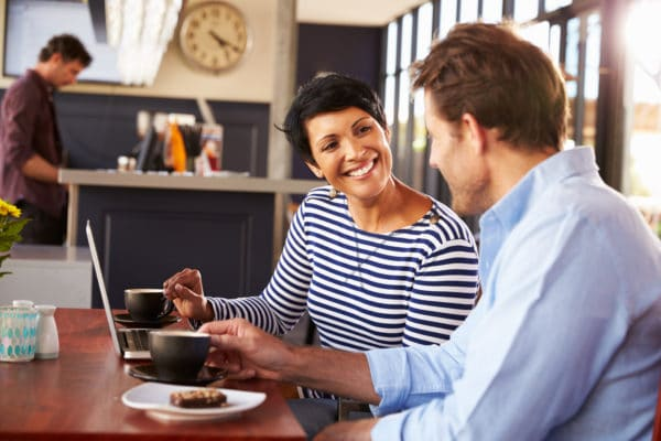 Man and woman meeting over coffee in a restaurant, smiling